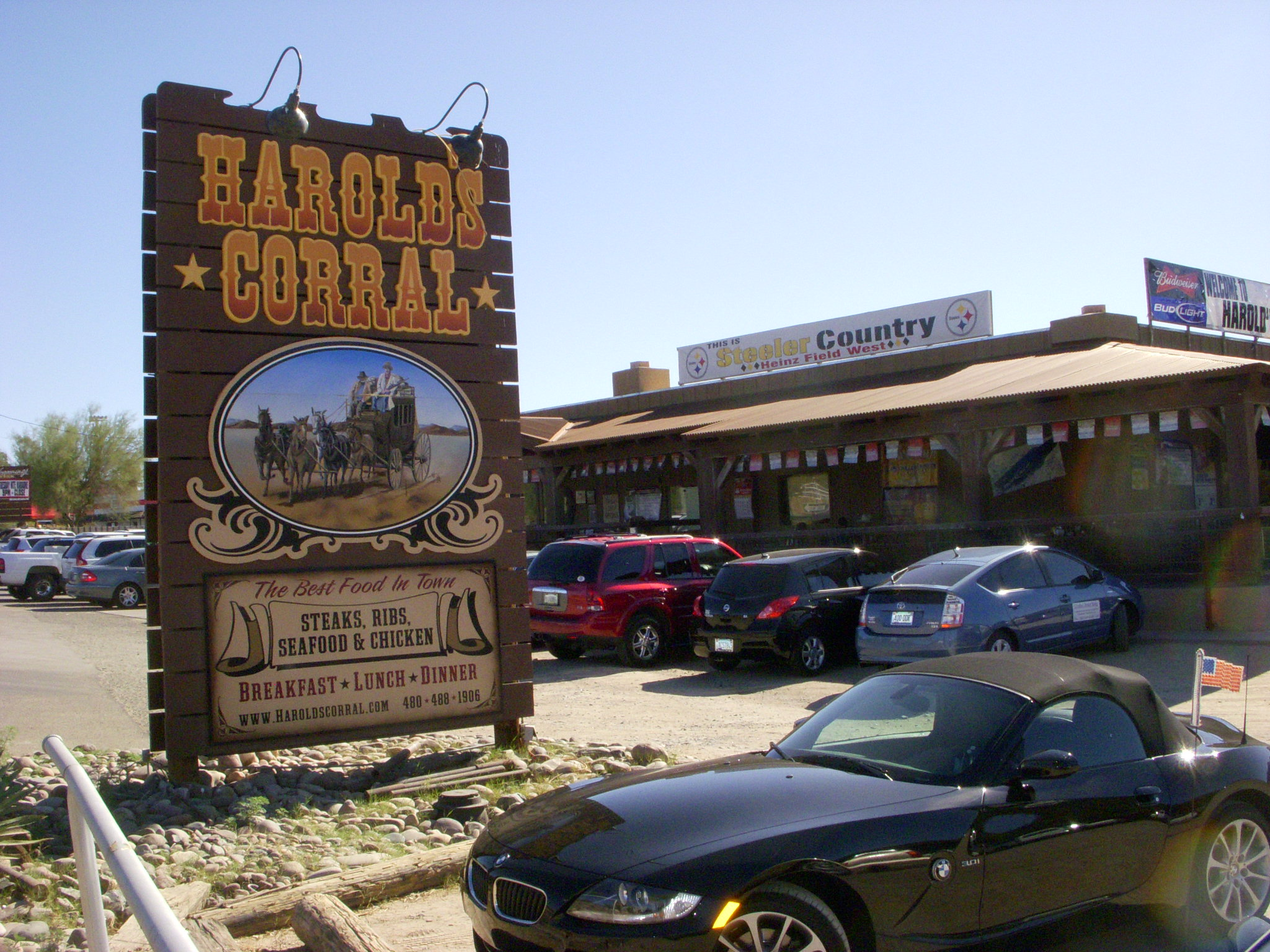 A view of Harolds Corral from the parking lot with a sign displayed on the building saying