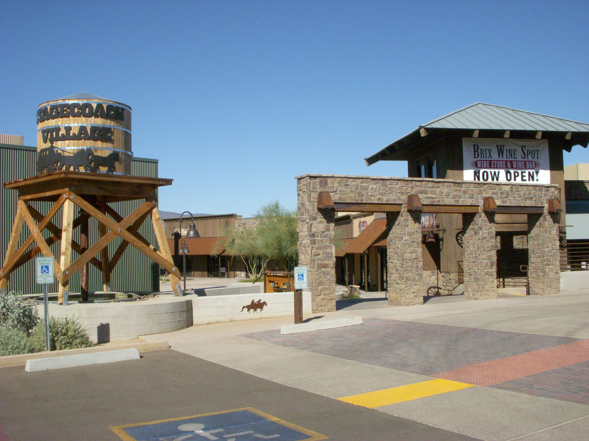 An outside view of the Stagecoach Village Shopping Center from the parking lot with a large wooden faux water tower with a stagecoach silhouette decoration.