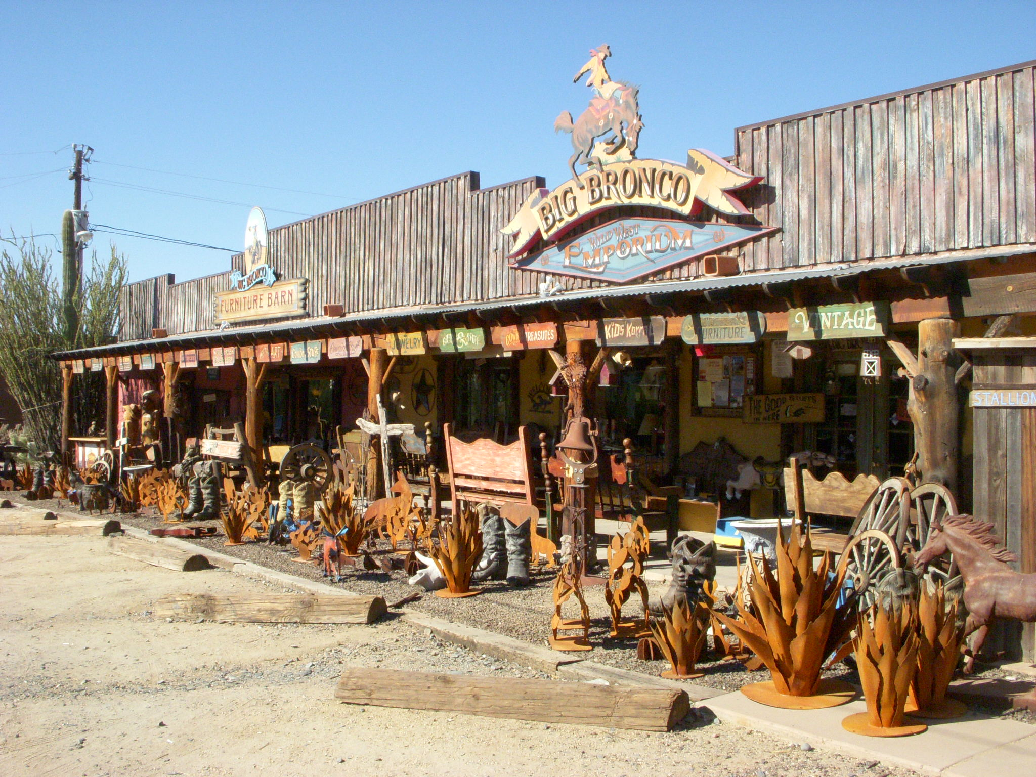 An outside view of the Big Bronco shop in Cave Creek with metal cacti and Western-themed artwork displayed out front.