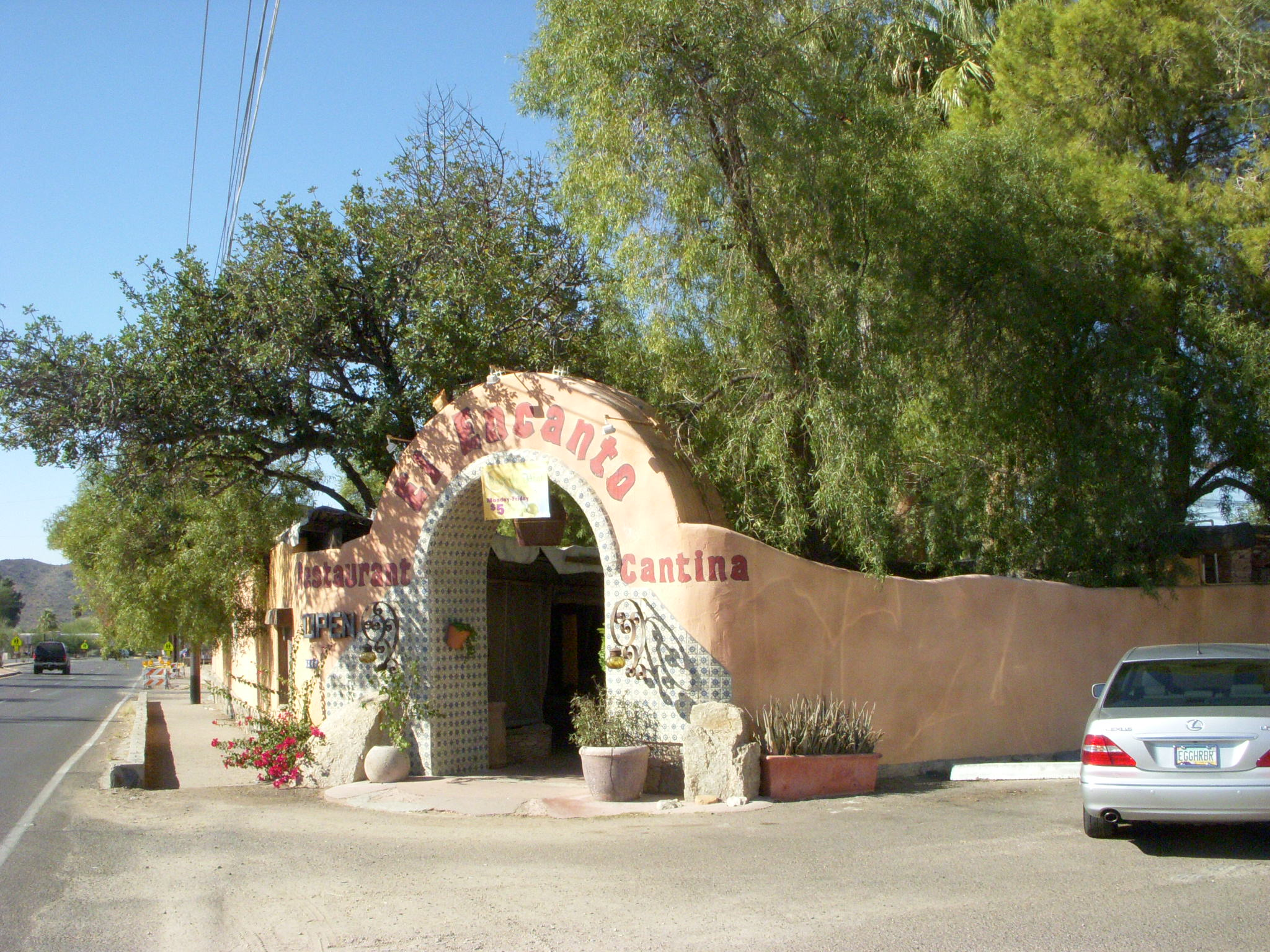 An outside view of El Encanto Restaurant that features its prominent adobe wall and entrance.